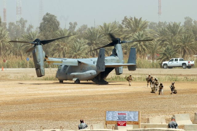 CAMP LIBERTY, Iraq - Marines (right) exit from the back of a MV-22B Osprey, a multi-mission, military tilt-rotor aircraft, at Camp Liberty March 19. Osprey aircraft routinely transport Marines, their supplies and equipment throughout the theater of operations in Iraq.