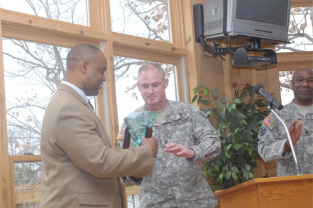 After speaking about the importance of teamwork and leadership, London receives the 8th Trans. Bde. Hero Award from its commander Col. Dan Georgi. London also made several parallels between his work and that of Soldiers, including the importance of recruiting, dependability and treating everyone in the organization with respect.