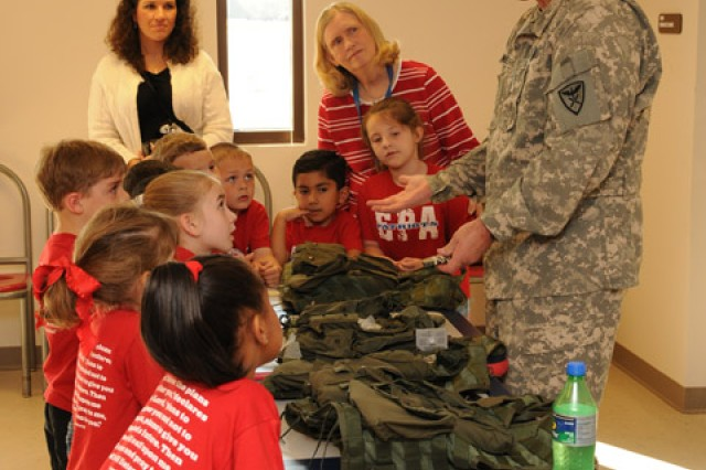 Fort Rucker Safety Officer CW4 Matt Wellinghurst, A Co., 1st Bn., 212th Avn. Regt. explains a flight vest and survival kit to a group of 5- and 6-year-olds from Enterprise Preparatory Academy. The class visited Shell Airfield March 19 to learn more about Army Aviation.