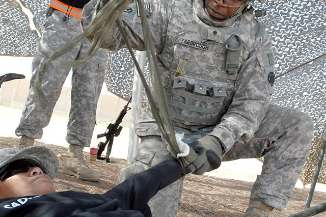 Spc. Mario D. Yarbrough from Memphis Tenn., gets timed by an evaluator as he performs first aid on another Soldier with a simulated bleeding extremity during the litter carry event of Sustainer Challenge at Joint Base Balad, Iraq, March 18. Yarbrough, a small arms repair a specialist with the 699th Maintenance Company out of Fort Irwin, Calif., competed with his team in the litter carry which is designed to test Soldier's endurance and knowledge of basic first aid. (U.S. Army photo by Spc. Brian A. Barbour)