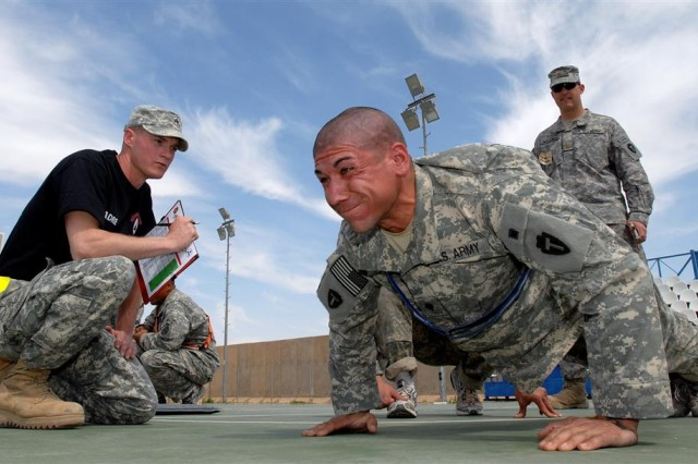 Sgt. James N. Stosh from Tampa Fla., grades Spc. Michael B. Leslie, from Dallas, Texas, on his push-ups as he participates in the physical training test event of Sustainer Challenge at Joint Base Balad, Iraq, March 18. Stosh a wheeled vehicle mechanic with the 330th Transportation Battalion from at Fort Bragg N.C., counted out 82 push-ups for Leslie, an infantryman running convoy security with the 2nd Battalion, 142nd Infantry Regiment out of Texas. (U.S. Army photo by Spc. Brian A. Barbour)
