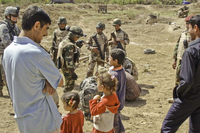 American and Iraqi troops interact with villagers near Forward Operating Base Hunter March 7. The village leader offered hot sweet tea, bread and bottled water to the troops.