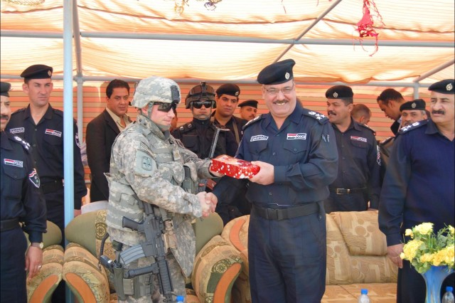 BAGHDAD - Before the recent Iraqi Police recruit graduation at Al Furat Iraqi Police Training Center, Maj. Robert Arnold, a native of Trenton, N.J., and chief of Baghdad Police Transition Team operations for 8th Military Police Brigade, received a token of thanks and appreciation from Brig. Gen. Ali Adnan Younis, Baghdad Provincial Director of Police, for his work on behalf of IP development Feb. 26.