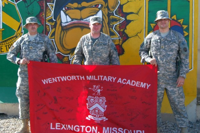 "CAMP LIBERTY, Iraq - Wentworth Military Academy graduates unfurled their school colors outside the 8th Military Police Brigade compound and showed ""Old Boy"" school pride for the Lexington, Mo., academy, March 11 at Camp Liberty.  Pictured from left to right are Lexington, Mo. native, Maj. John Crews of the 8th MP Bde., Staff Sgt. John Trott, 340th MP Company, 91st MP Battalion, 8th MP Bde. of Pleasant Hill, Mo. and Maj. Aubrey Hinds of Multi-National Corps-Iraq, who hails from Plano, Texas. All three are graduates of the Class of 1995.The Wentworth graduates presented the flag to the 1st Cavalry Division, Multi-National Division-Baghdad dining facility for display in honor of those Wentworth Military Academy grads who serve in the military and have served in support of Operation Iraqi Freedom and Operation Enduring Freedom."