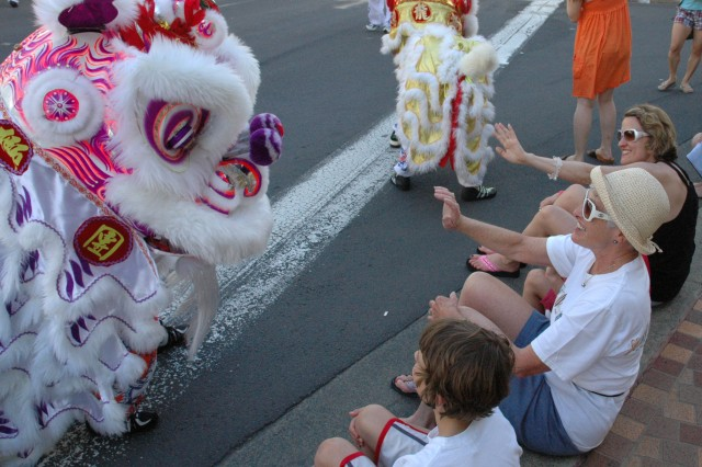 WAIKIKI, Hawaii - Seattle resident Will Allen, 8, looks on as his grandmother and mother, Anne Ransom (center) and Mary Ransom wave to a passing dragon during the grand parade in Waikiki, March 15, for the Honolulu Festival.