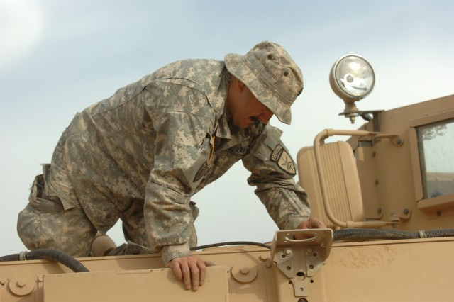Navy Chief Nathan Montes, a Bronx, N.Y. native attached to 3rd Brigade Combat Team, 25th Infantry Division, performs routine maintenance on a Caiman mine resistant ambush protected vehicle at Forward Operating Base Bernstein, Iraq, March 19. (U.S. Army photo by Pfc. Jesus J. Aranda, Task Force Lightning Public Affairs)