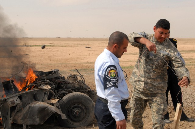 Iraqi Police Sgt. Maj. Omar Salim, sergeant major of the Salah ad-Din Iraqi Police EOD team, shows a fellow policeman how to collect and remove evidence from a supervised blast site. IP's applied advanced crime scene investigation techniques they learned from Coalition forces EOD during a series of training exercises March 18.
