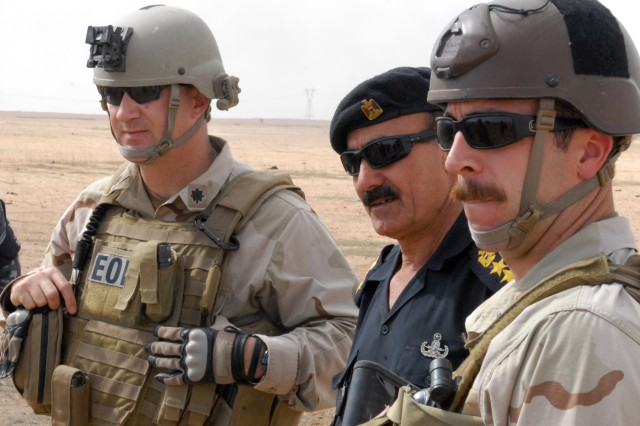(From left to right) Navy Commander Eric Wirstrom, commander, Explosive Ordnance Disposal, Mobile Unit One, Iraqi Police Lt. Col. Abdul al-Hadi, commander, Salah ad-Din Iraqi Police Explosive Ordnance Disposal team, and Navy Petty Officer First Class Neil Marshall observe training at a demolition range at Contingency Operation Base Speicher, near Tikrit, Iraq, March 18.