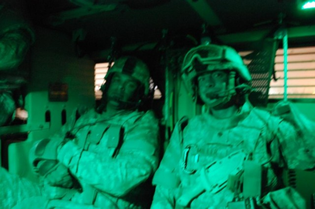 CAMP Taji, Iraq - Sgt. Eddie Davis and Spc. Rocky Miller, of the Forward Support Company, 4th Engineer Battalion, 225th Engineer Brigade, conduct night maintenance operations near Camp Taji, Iraq March 15, to recover a broken down route clearance vehicle.