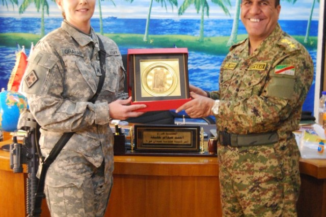 MUTHANA, Iraq - Sgt. Catherine Graham (left) of the 890th Engineer Battalion, 225th Engineer Brigade was presented an award from Col. Ahmed Saddam (right), commander of the 6th Iraqi Army Regiment Engineers March 10, in recognition for her hard work and dedication, during her one-year deployment as the battalion's public affairs representative.