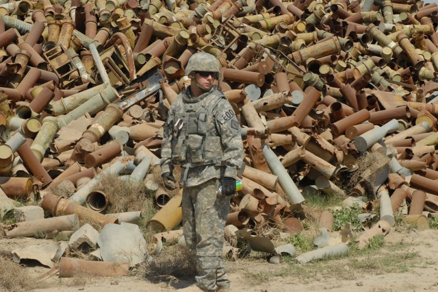Sgt. Robert Solesbee, a native of Corona, Calif., assigned to 710th Explosive Ordnance Disposal Company, 3rd Ordnance Battalion, 71st Ordnance Group, glances around at his surroundings, looking for potentially dangerous ordnance among the scrap metal at the Sheik Khalid scrap yard March 18.