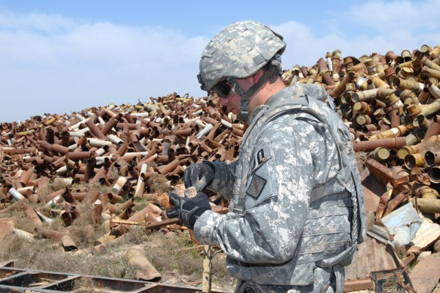 CAMP TAJI, Iraq - Sgt. Robert Solesbee, assigned to 710th Explosive Ordnance Disposal Company, 3rd Ordnance Battalion, 71st Ordnance Group and a native of Corona, Calif., examines fuses from unexploded ordnance found among piles of scrap metal to assess if they are potentially dangerous March 18.