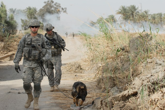 Sgt. Christopher Jasper (left), a kennel master from Everett, Wash., and his German Sheppard, Uwe, assigned to the Provost Marshall's Office, Camp Liberty K-9 section, 1st Cavalry Division, look for unexploded ordnance, weapon caches and improvised explosive devices  March 21, along with 1st Lt. Thomas Ray, a native of Freemansburg, Pa.