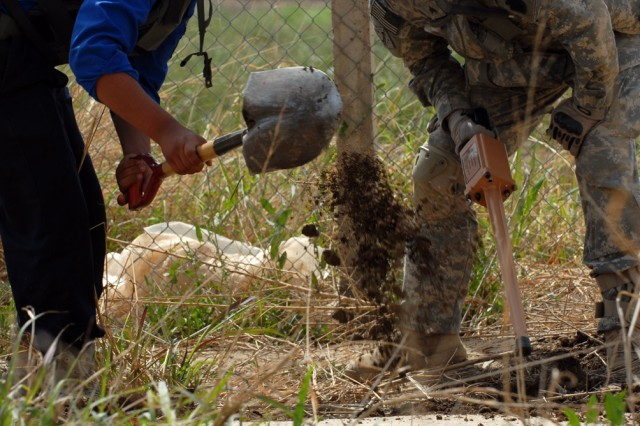 Sgt. Michael Tornincasa (right), from Struthers, Ohio, assigned to the 2nd Battalion 'Strykers,' 112th Infantry Regiment, 2nd Brigade Combat Team, 1st Infantry Division, yells words of encouragement to an Iraqi policeman while digging a hole where the metal detector detected an object.