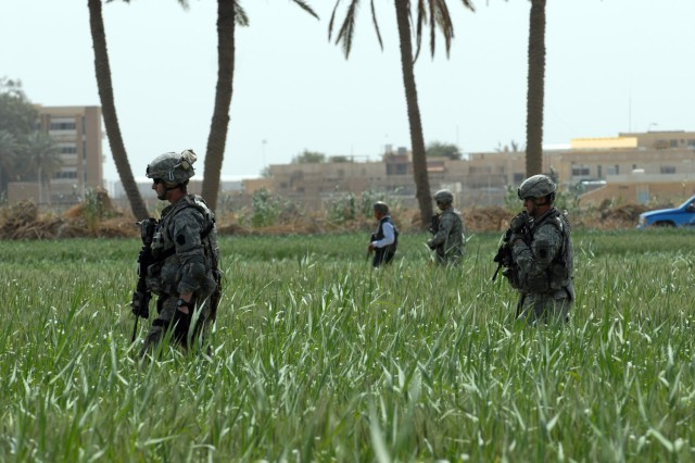 """Stryker"" Soldiers from the 2nd Battalion, 112th Infantry Regiment, 2nd Brigade Combat Team, 1st Infantry Division and Iraqi policemen clear one of many fields surrounding the Baghdad University College of Agriculture in Abu Ghraib March 21."