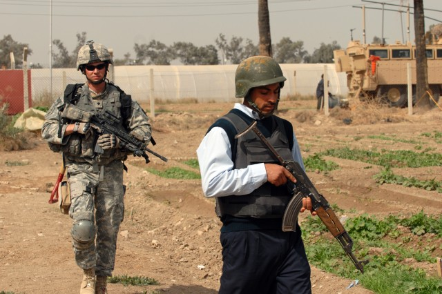 Spc. Dane Bamford (left), from Shamokin, Pa., assigned to the 2nd Battalion, 112th Infantry Regiment, 2nd Brigade Combat Team, 1st Infantry Division, searches with an Iraqi policeman during a joint operation at Baghdad University College of Agriculture in Abu Ghraib March 21.