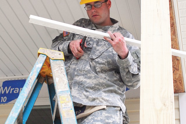 Pfc. Vincent Tomasino, a volunteer in the 11th Engineer Battalion, trims the j-channel, which he must lay down before adding siding to the Habitat for Humanity house Friday.