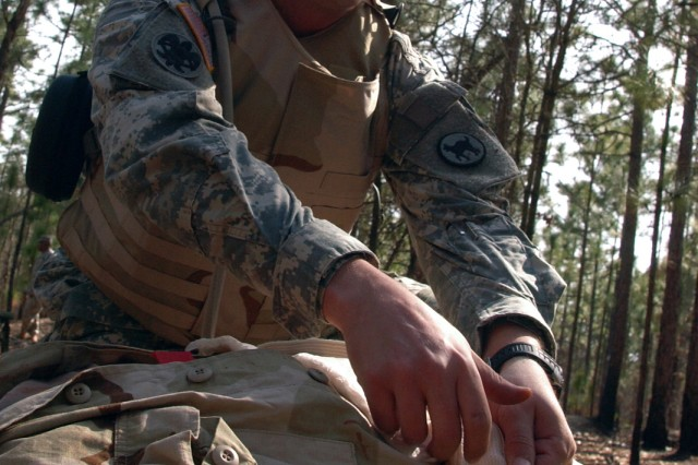 """Staff Sgt. Renaldo Rivera, 81st Regional Support Command, based at Fort Jackson, S.C., applies an abdominal dressing to a """"casualty"""" during the warrior tasks portion of the 81st RSC's Best Warrior Competition held here March 20-22. The competitors were competing for spots in next month's regional competition held here."""