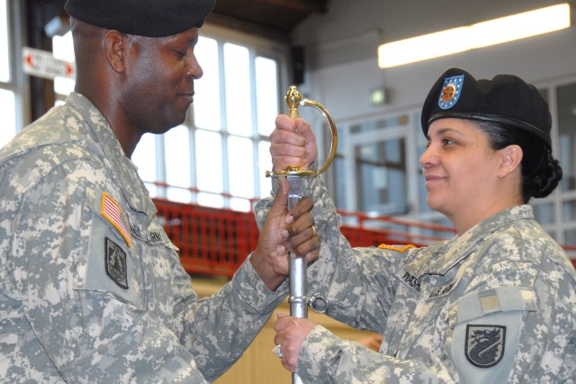 Command Sgt. Maj. Donald Manley, Network Enterprise Technology Command/9th Signal Command, passes the noncommissioned officer sword of responsibility to Command Sgt. Maj. Marilyn Washington, symbolizing her acceptance of becoming 5th Signal Command's new command sergeant major during a change of responsibility ceremony at the sports arena on Sullivan Barracks.