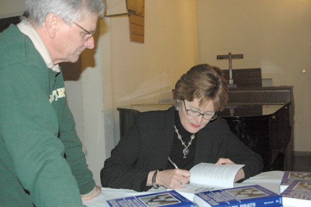 """Mary Edwards Wertsch, military family researcher and author of """"Military Brats: Legacies of Childhood Inside the Fortress,"""" autographs a copy of her book after leading a discussion at Mark Twain Village Chapel in Heidelberg March 18."""