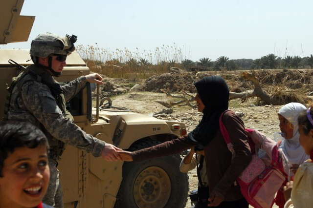 BAGHDAD - Sgt. Todd Troiani of Company A, 1st Combined Arms Battalion, 63rd Armor Regiment, who hails from Woodland, Maine shakes hands with a student of Al-Khaladeen School after a ribbon cutting ceremony in Lutifiyah March 19.