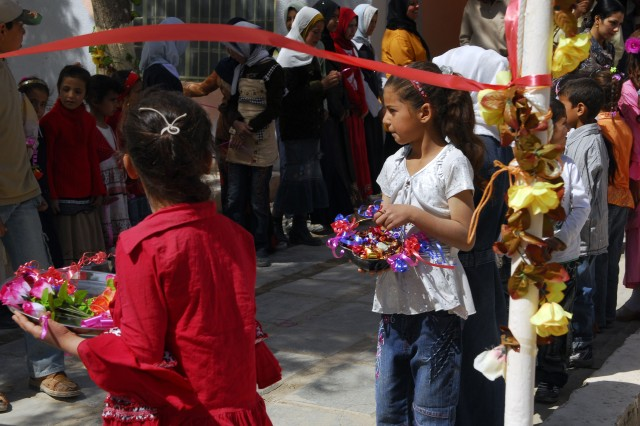 BAGHDAD - Students wait by the ribbon before it is cut March 19 in Lutifiayah to celebrate the opening of Al-Khaladeen School after receiving a major refurbishment.
