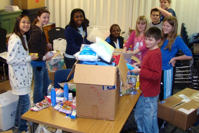 Humphreys American School middle and elementary school student council members pack more than 25 cases of Humanitarian Aid items for Iraqi children and their families, Feb. 24.