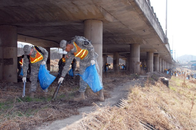 Participating in the 2009 Spring Riverfront Clean-up, along Dongducheon City's portion of the Shincheon River, are Pfc. Aaron Elwell (left) and Pfc. Evan Spruill of the 579th Signal Company. More than 150 USAG-Casey Soldiers from the 210th Fires Brigade and their supporting elements partnered with local citizens and city officials March 20. City volunteers, along with support from USAG-Casey's USO staff, were also on hand to pass out light snacks and beverages. - U.S. Army photo by Jack Loudermilk