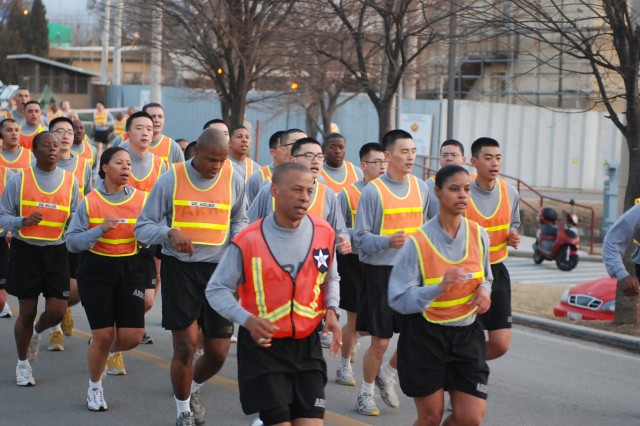 "Warrior Country noncommissioned officers led by Command Sgt. Maj. Peter Burrowes (front left), 2nd ID Command Sgt. Maj. and Earlene Lavender (front right), USAG-RC Command Sgt. Maj., run through Uijeongbu city singing cadence in the NCO 5K Run. The run was one of the many events Warrior Country NCO's have prepared in celebration of the ""Year of the NCO."""
