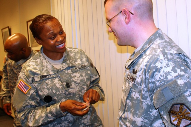 HHD, USAG Schinnen Sgt. 1st Class David S. Clark receives a coin from IMCOM-Europe Command Sgt. Maj. Tracey E. Anbiya during her visit to USAG Schinnen March 19.