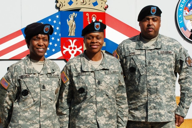 IMCOM-Europe Command Sgt. Maj. Tracey E. Anbiya (center) pauses in front of USAG Schinnen headquarters with USAG Benelux Command Sgt. Maj. Ralph Ford (right) and USAG Schinnen Command Sgt. Maj. Mary L. Brown during a visit there March 19.