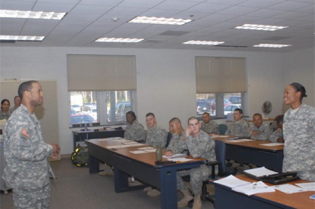 Sgt. Lawrence Taylor, left, listens to a Soldier introduce herself on the first day of class Tuesday at the Simulation Training Center on Fort Eustis for the cargo specialist course (88H), which Taylor instructs with a team of several noncommissioned officers. His newest class has 20 students. Taylor has been a cargo specialist instructor since September 2006.