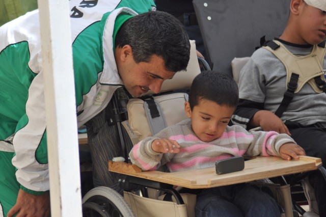 An Iraqi boy and his father share a moment as they look at a cell phone on the boy's new wheelchair March 23, in the Rusafa District of eastern Baghdad.