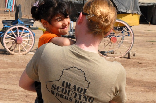 CAMP VICTORY, Iraq - Sgt. Shannon LeMaster, an imagery analyst with the 301st Military Intelligence Battalion, Multi-National Corps - Iraq, welcomes Tabarak, age 4, to another fun-filled day of Iraqi Scouting March 21. LeMaster, a native of Phoenix, Ariz., volunteers her free time with the Victory Base Council to promote the fledgling scouting movement and teach the youth of Iraq new things.