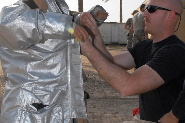 CAMP VICTORY, Iraq - Air Force Senior Airman Mike Manzer, a firefighter with the 447th Civil Engineer Fire Department, Sather Air Base, gets 10-year-old Ahmed suited up in reflective fire-fighting gear March 21. The suit is dubbed 'proximity gear' because its material enables a firefighter to get closer to fight fuel fires. Ahmed then climbed into the fire truck and gave commands on the truck's public address loudspeaker.