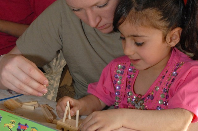 CAMP VICTORY, Iraq - Taiba, 5, works on inserting wooden pegs that will support the top wing assembly of a wooden model plane with Sgt. Shannon LeMaster, an imagery analyst with the 301st Military Intelligence Battalion, Multi-National Corps - Iraq March 21.