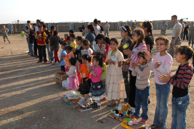 CAMP VICTORY, Iraq - Happy children and volunteer service members line up to celebrate a successful day of scouting activities and fun before beginning the closing ceremony March 21. Each week, the children are exposed to a new scouting lesson, an arts and craft project, and sporting activity to help build awareness, character, and good health.