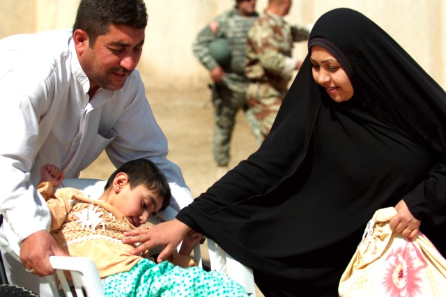 BAGHDAD-An Iraqi couple braces their child in his new wheelchair as they lower him off a sidewalk.   The wheelchair, provided by the 11th Iraqi Army Division, was part of a humanitarian aid mission at the New Iraq School in the Adhamiyah district of Baghdad March 19.