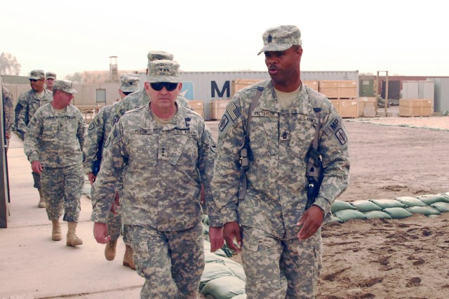 CAMP LIBERTY, Iraq - Command Sgt. Maj. Norwood Patterson III (right), command sergeant major of the 8th Military Police Brigade, Multi-National Division-Baghdad, and a native of Lenoir, N.C., leads Lt. Gen. Benjamin Mixon (left), commander of United States Army Pacific Command, Fort Shafter, Hawaii, and staff members on a tour of the Watchdog Compound March 24. Mixon, who deployed to Iraq in 2006-07, emphasized that NCOs need to take care of their Soldiers and let his Soldiers know that Hawaii appreciates their service and sacrifice.