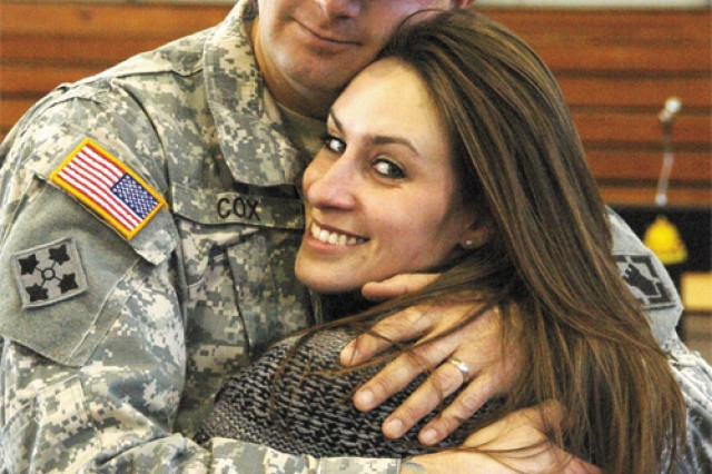Staff Sgt. Wes Cox, assigned to the 86th Engineer Dive Team, embraces his wife, Katie, prior to a departure ceremony held Monday at Anderson Field House. The dive team is taking part in a year-long deployment to Kuwait Naval Base in support of Operation Iraqi Freedom.
