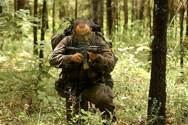 Staff Sgt. Aaron Parrott, a student in the Reconnaissance and Surveillance Leader Course, takes a break from firing to look for opposing forces during a field exercise Tuesday afternoon. The RSLC, offered five times annually by D Company, 4th Ranger Training Battalion, is available to any soldier assigned to or with the potential to be assigned to a long range surveillance or reconnaissance-type unit.
