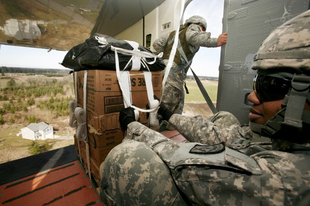 Staff Sgt. Dawn Bryant, 24th Quartermaster Company, 593rd Sustainment Brigade, prepares to drop a supply load from a Sherpa cargo plane, March 6, as part of Low Cost Low Altitude delivery system training.