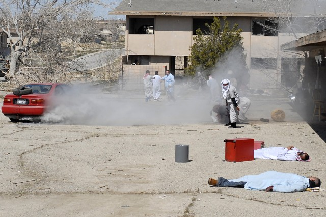 Iraqi role players react to injured civilians as a VBIED smokes after exploding in a market during 1-23 Inf.'s training exercise March 12 at the Southern California Logistics Airport.