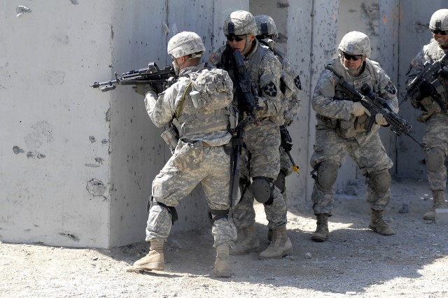 Soldiers from B Co., 1-23 Inf., ready to move to another building during a joint training exercise with the United States Marine Corps' 1st Tank Battalion Sunday at Marine Corps Air Ground Combat Center Twentynine Palms, Calif.