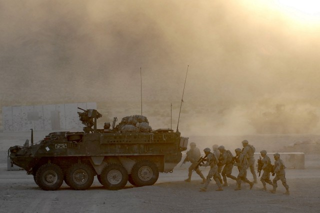 Soldiers from B Co., 1-23 Inf. use a Stryker as cover while moving to clear a building during a joint training exercise Tuesday with the Marine Corps 1st Tank Battalion at Marine Corps Air Ground Combat Center Twentynine Palms, Calif.