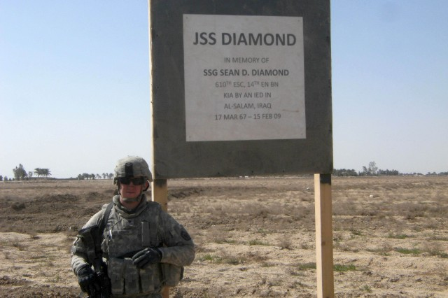 Specialist James Saunders stands by the sign he built honoring his former squad leader, Staff Sgt. Sean D. Diamond.
