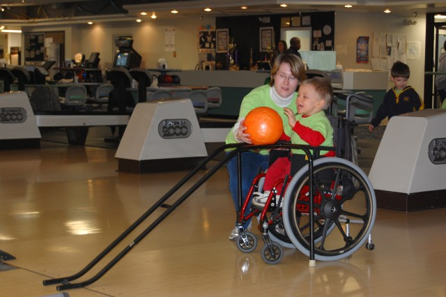 Amber Wright, early childhood special education teacher, assists her student, Daniel McRae, during a special class outing March 20 at the Fort Lee Bowling Center.