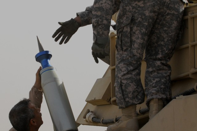 An Iraqi Armor School student (left) lifts a Sabot round to Staff Sgt. Joseph Romano as they load the M1A1 Abrams in preparation for Iraqi tankers to receive training from Soldiers of MNSTC-I and contracted instructors at Besmaya range, March 21.