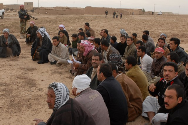 "Adult males wait outside of their village while Iraqi Army, Iraqi Police and Soldiers from 4th Squadron, 9th Cavalry Regiment, 2nd Brigade Combat Team, 1st Cavalry Division conduct operation ""Dark Horse Cossack Two"" in the village of Yourgun, March 15. During the operation, IP's executed warrants and captured detainees wanted for various crimes."