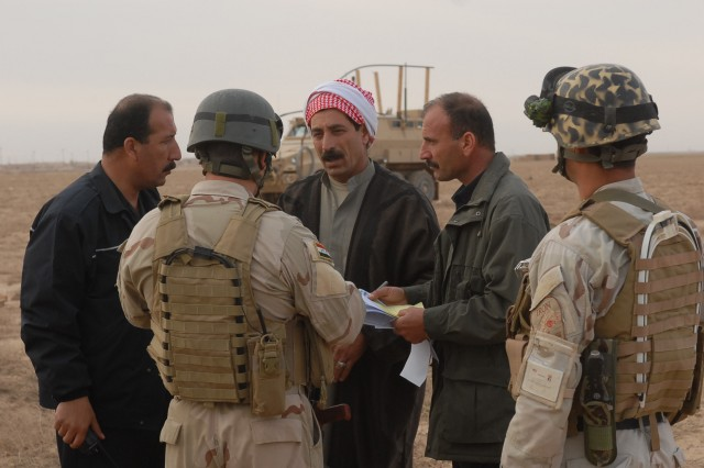 """Iraqi Police and Iraqi Army talk to the village leader, known as a Muktar, during operation """"Dark Horse Cossack Two"""" March 15. The operation was conducted in the village of Yourgun, Kirkuk, Iraq, and was lead by IA and IP with assistance from U.S. military."""